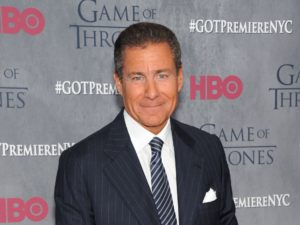 HBO's CEO Richard Plepler stands front of a promo for a Game of Thrones season premiere